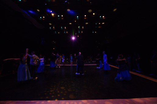 Dancers and audience members dance.